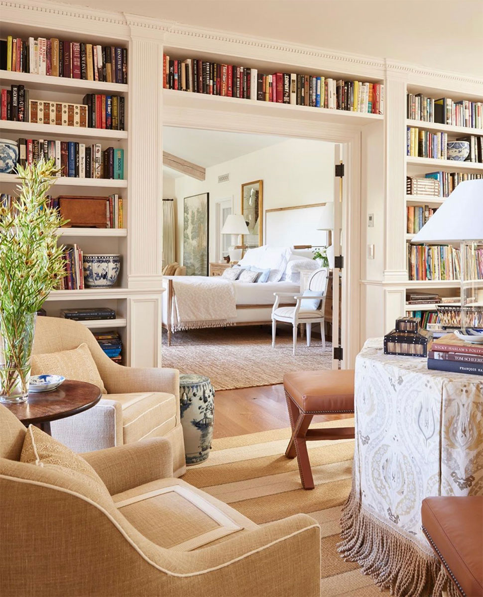 Encased door with wall of bookshelves featured in the Atlas Concorde USA blog by Mark D. Sikes Interiors
