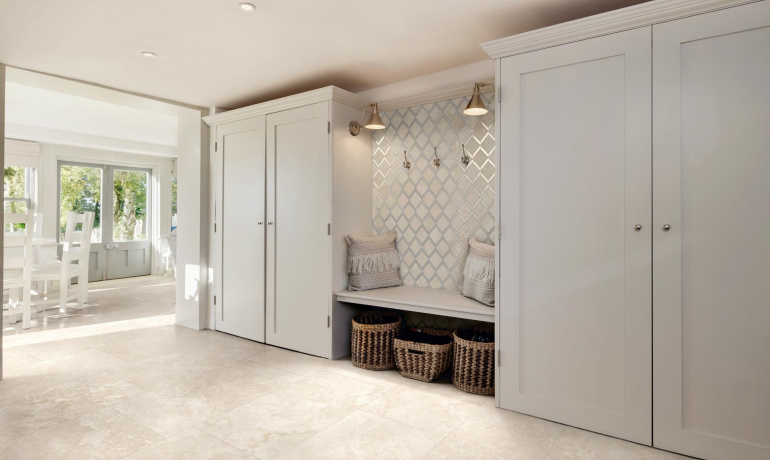 Open mudroom with travertine-looking porcelain tiles by Atlas Concorde USA